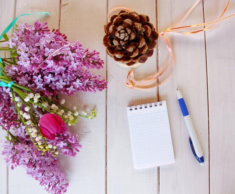 Draufsicht des Arbeitsplatzes, mit dem Rand eines Blumenstraußes der Flieder stockfotografie