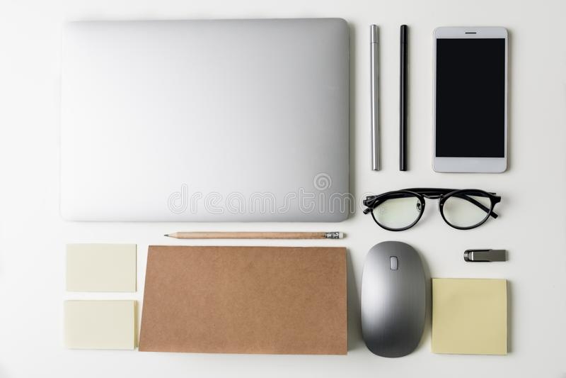 Draufsicht des Büro-Arbeitsplatzes Flache Lageansicht über weiße Tabelle mit Laptop, Telefon, Notizbuch, Stifte, Aufkleber, Gläse lizenzfreies stockfoto