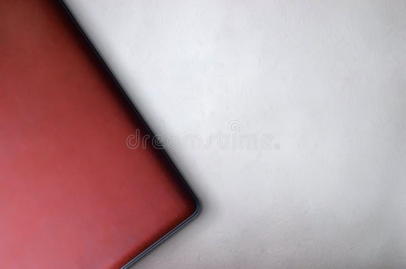 Draufsicht des besten Hintergrundes des roten Laptops für Darstellungsschablone stockfotografie