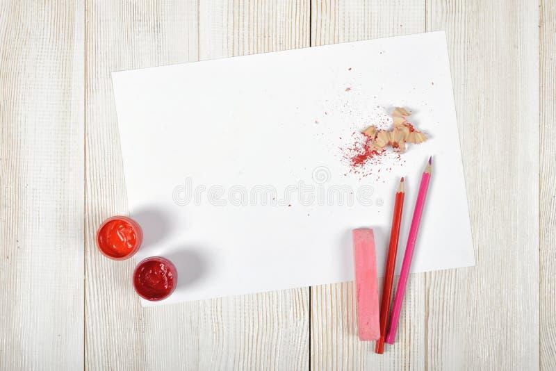 Draufsicht des Designerarbeitsplatzes ausgerüstet mit rot-rosa Gouachegläsern, farbigen Bleistiften, Kreide, Schnitzeln und Weißb lizenzfreies stockbild