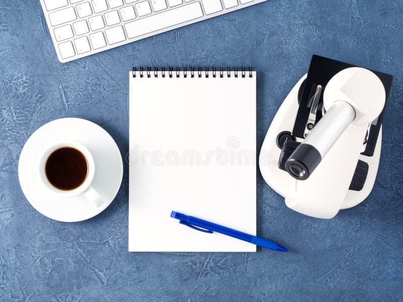 Draufsicht des dunkelblauen Desktops mit Mikroskop, Notizblock, Computer Verspotten Sie oben, leerer Raum, Wissenschaftsschablone lizenzfreies stockfoto