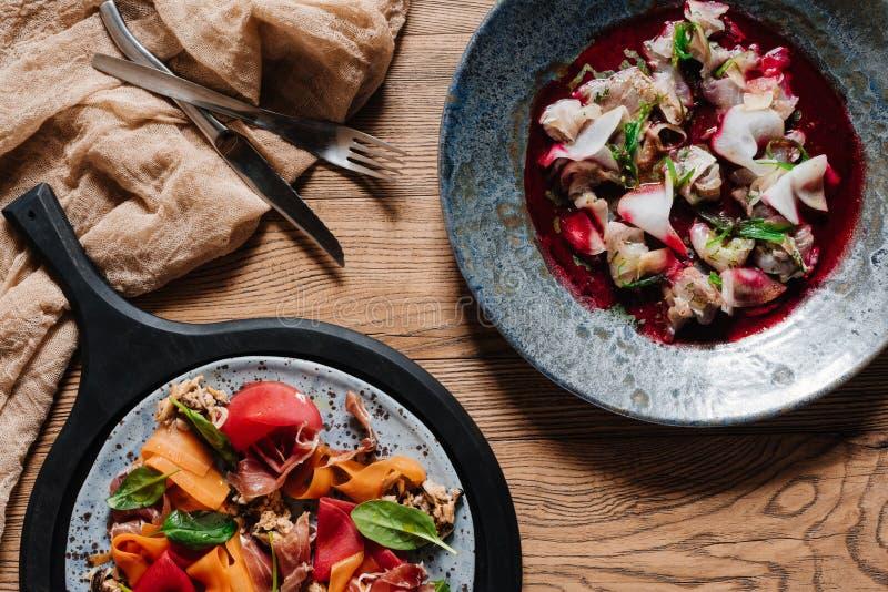 Draufsicht des feinschmeckerischen Salats mit Miesmuscheln und des köstlichen ceviche mit dorado auf Holztisch stockbild