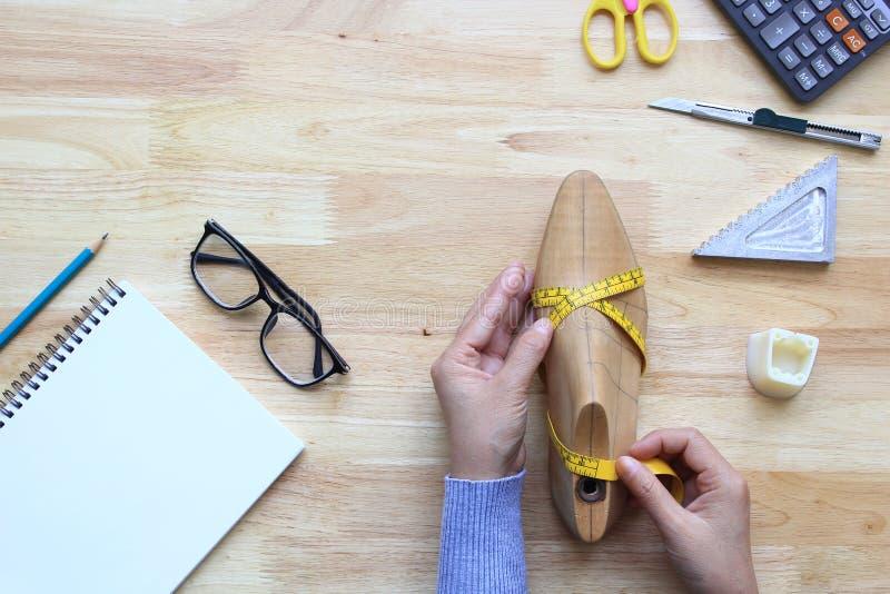 Draufsicht des Frauenhandmessenden Bands auf hölzernem letztem Schuh auf hölzernem Hintergrund mit copyspace stockfotografie