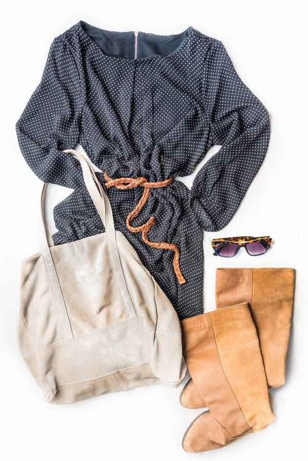 Draufsicht des Frauenkleidungssatzes Schwarzes punktierte Kleid, braune Lederstiefel und Zubehör über weißem hölzernem Hintergrun lizenzfreie stockbilder