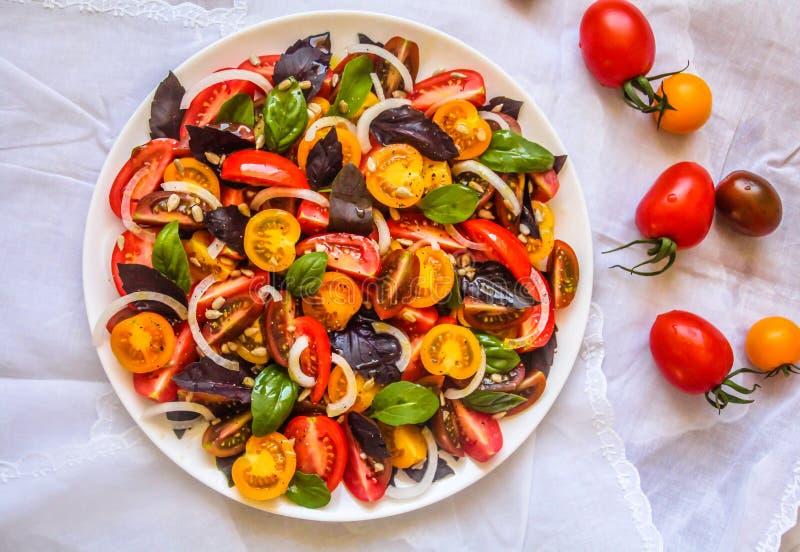 Draufsicht des frischen roten u. gelben Kirschtomatensalats und der grünen und roten Basilikumblätter stockbilder