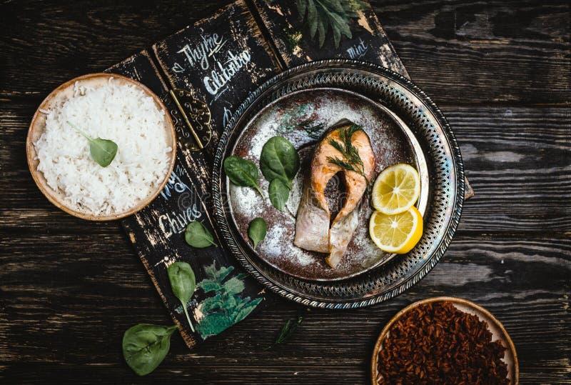 Draufsicht des gebackenen Lachssteaks mit Zitrone auf rustikalem Metallbehälter mit Reisbeilage stockfotografie