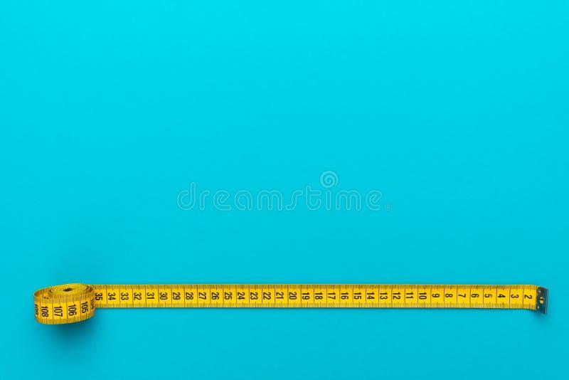 Draufsicht des gelben messenden Bands über Türkisblauhintergrund mit Kopienraum stockbilder