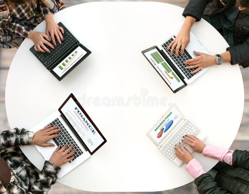 Draufsicht des gerundeten Schreibtisches mit vier Laptops und Leute-Händen, die auf Tastatur schreiben lizenzfreie stockfotos