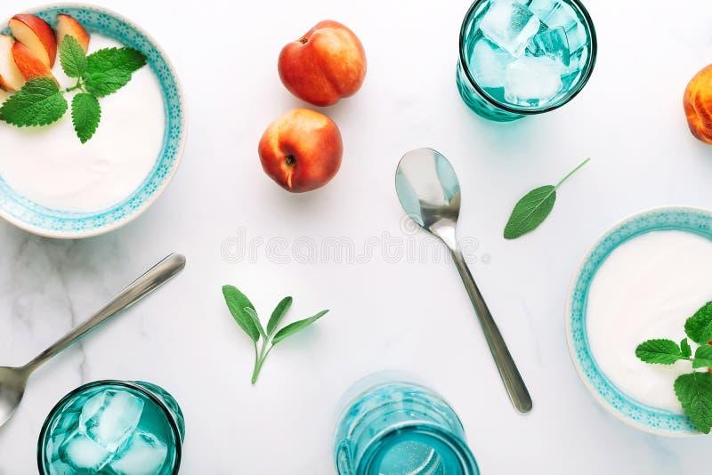 Draufsicht des gesunden Frühstücks des natürlichen griechischen Joghurts, der Frucht und des Wassers auf Marmortabelle Flache Lag lizenzfreie stockfotos