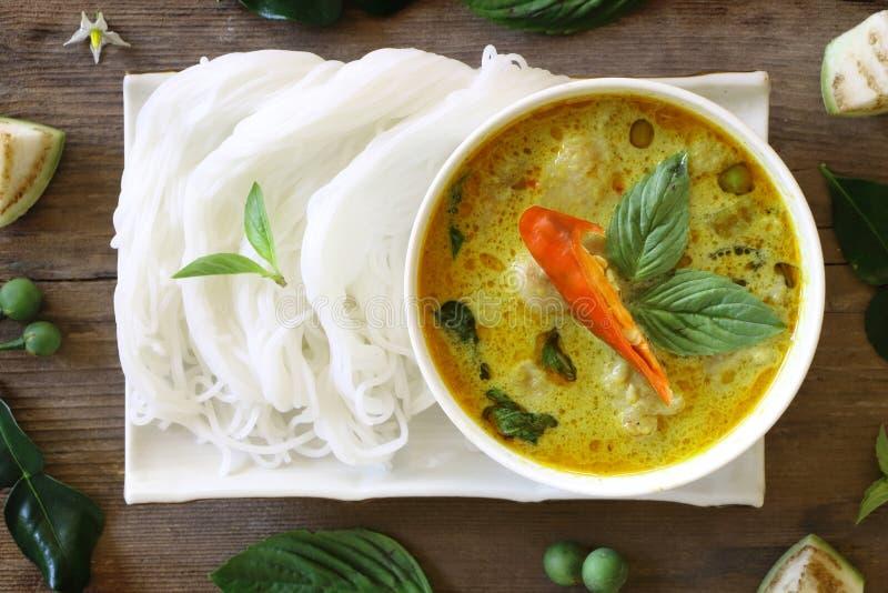 Draufsicht des grünen Curryfischballs diente mit thailändischen Reissuppennudeln in der weißen Platte auf hölzerner Tabelle, der  lizenzfreies stockfoto