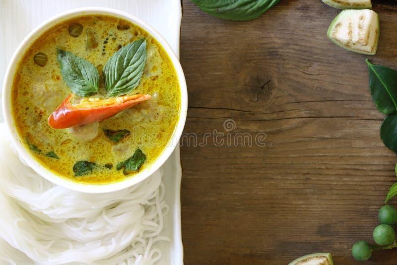 Draufsicht des grünen Curryfischballs diente mit thailändischen Reissuppennudeln in der weißen Platte auf hölzerner Tabelle, der  lizenzfreie stockbilder