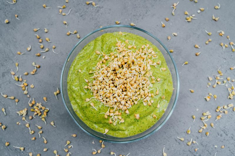 Draufsicht des grünen Smoothietellers in der Schüssel mit grünen Buchweizensprösslingen Gemüseteller des gesunden Frühstücks Mahl stockfotos