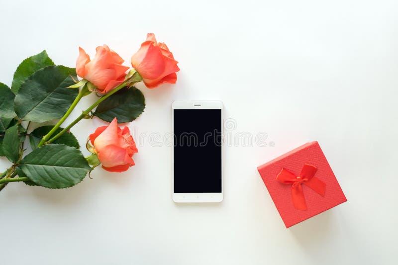 Draufsicht des Handys mit Kopienraum, roter Geschenkbox und Rosen stockbild