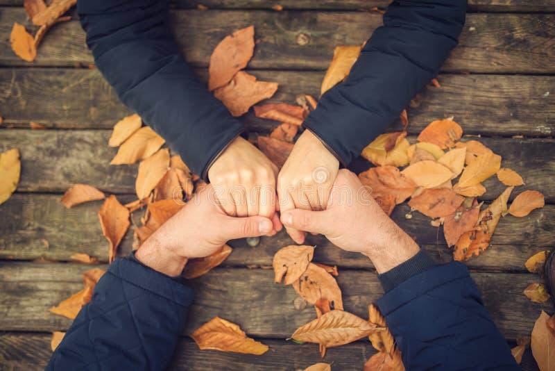 Draufsicht des Herbstpaarhändchenhaltens Herbstliches Verhältnis-Liebeskonzept stockfotografie