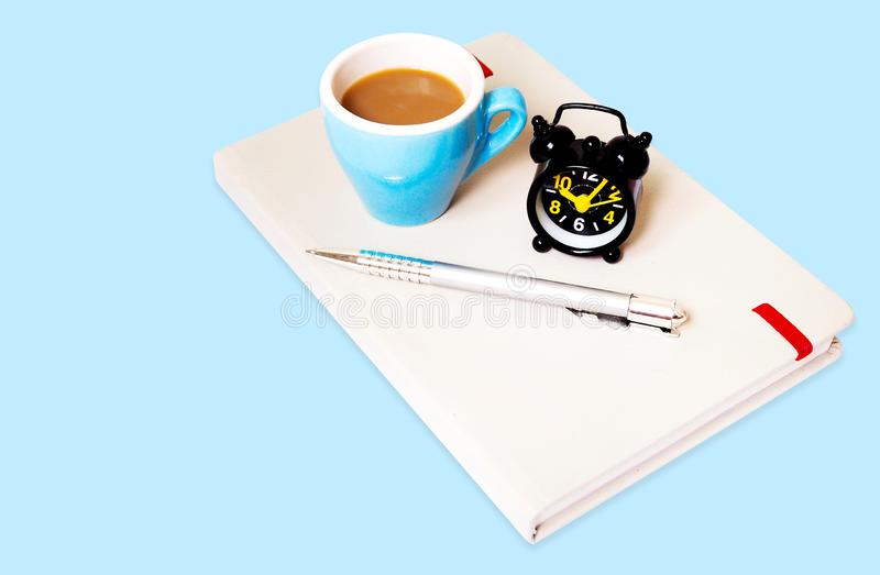 Draufsicht des Hintergrundschablonenentwurfs mit Kaffeetasse, Wecker und Notizbuch auf blauem Papier stockbild