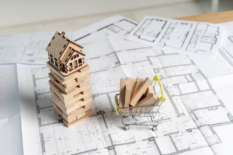 Draufsicht des hohen Winkels des kleinen Holzhauses auf jenga Blöcke mit errichtendem Plankenbrett im kleinen Einkaufswagenstand  lizenzfreie stockbilder
