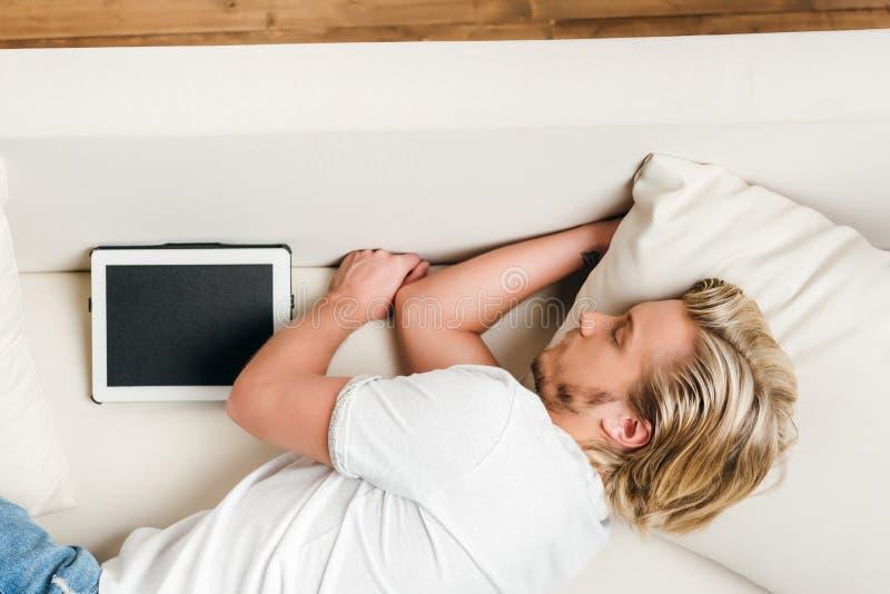 Draufsicht des jungen blonden Mannes mit digitaler Tablette schlafend auf Sofa stockfoto