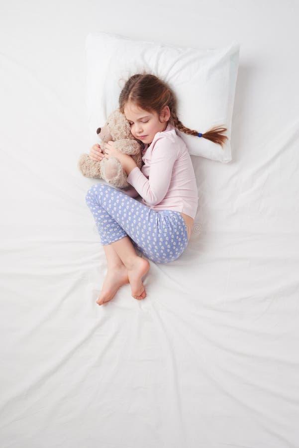 Draufsicht des kleinen netten Mädchens, das mit Teddybären schläft lizenzfreie stockfotografie