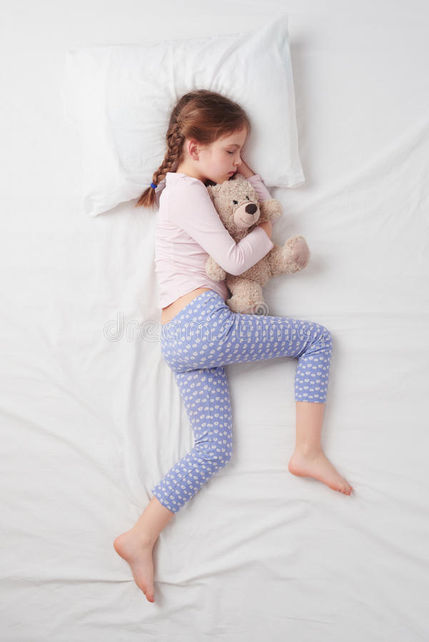 Draufsicht des kleinen netten Mädchens, das mit Teddybären schläft lizenzfreie stockbilder