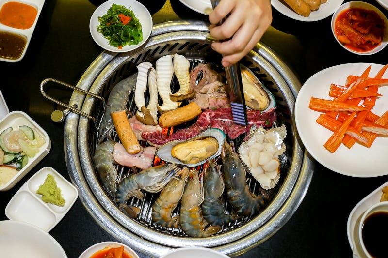 Draufsicht des koreanischen Artgrills, des sortierten Fleisches und des Meeresfrüchte gri stockbild