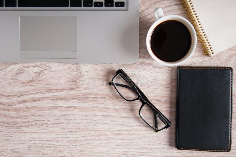 Draufsicht des Laptops und des Notizblockes mit Gläsern und Taschenbuch auf dem hölzernem Desktop und Tasse Kaffee stockbild