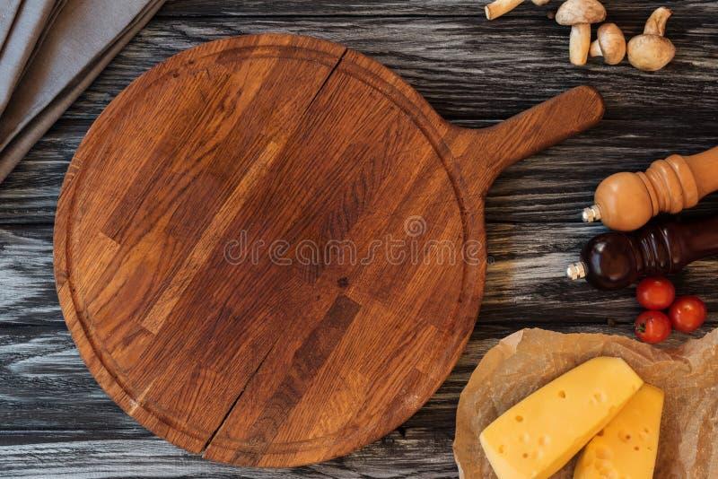 Draufsicht des leeren hölzernen Schneidebretts, der Gewürze, des Käses und des Gemüses stockbild