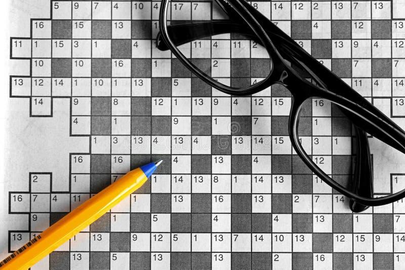 Draufsicht des leeren Kreuzworträtsels mit Brillen und einem p lizenzfreies stockbild