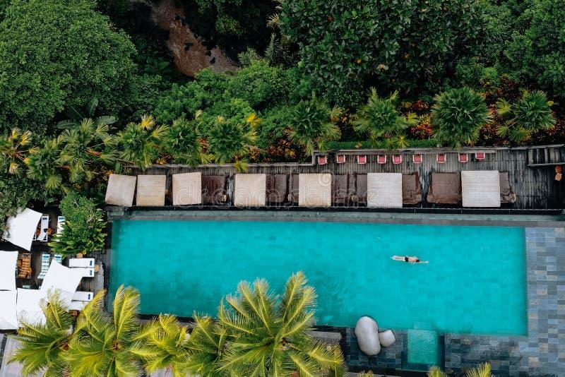 Draufsicht des Luxuspools mit Regenschirmen und Schwimmen um Palmen und Dschungel Sch?ne junge Frau an einem Pool Brummen-Foto stockfoto