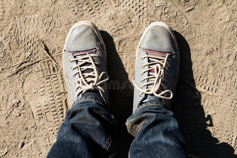 Draufsicht des Mannfußes mit Trekkingsschuhen auf Erdgeschosshintergrund stockfotografie