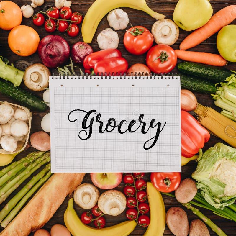 Draufsicht des Notizbuches mit Wortlebensmittelgeschäft auf Gemüse und Früchten lizenzfreie stockbilder