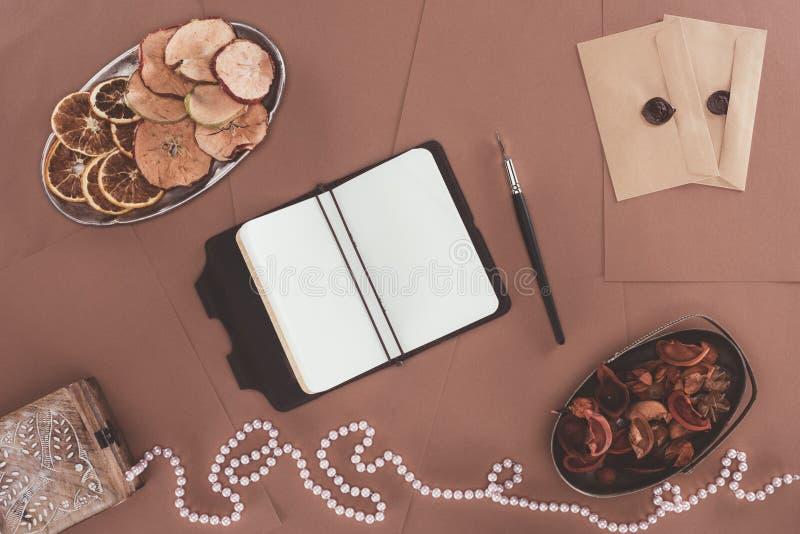 Draufsicht des Notizbuches, des Schmuckkästchens, der Trockenfrüchte und der Umschläge über Braun stockbild
