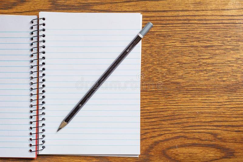 Draufsicht des offenen gewundenen Notizbuches mit schwarzem Bleistift auf Schreibtischhintergrund stockfotografie