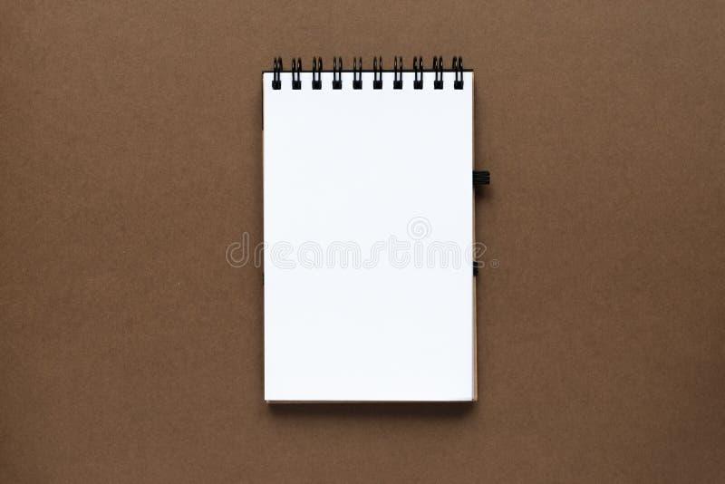 Draufsicht des offenen leeren Notizbuches mit Abdeckung vom Recyclingpapier auf braunem buntem Hintergrund lizenzfreie stockbilder
