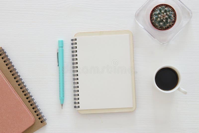 Draufsicht des offenen Notizbuches mit Leerseiten nahe bei Tasse Kaffee auf Holztisch bereiten Sie für das Addieren des Textes od stockfotografie
