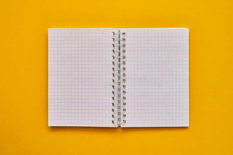 Draufsicht des offenen Notizbuches mit Leerseiten Schulnotizbuch auf einem gelben Hintergrund, gewundener Notizblock stockfotos