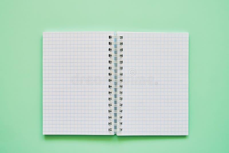 Draufsicht des offenen Notizbuches mit Leerseiten, Schulnotizbuch auf einem grünen Hintergrund, gewundener Notizblock stockbilder