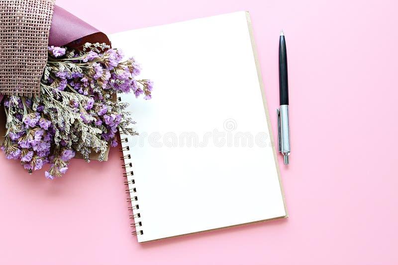 Draufsicht des offenen Notizbuchpapiers mit Leerseiten und des Blumenstraußes der getrockneten wilden Blumen auf rosa Hintergrund stockfoto