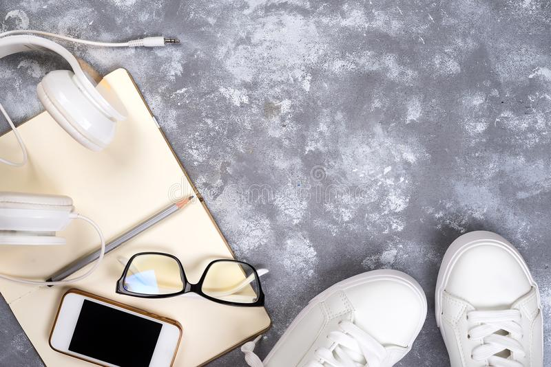 Draufsicht des Reisematerials Wesentliche Reiseeinzelteile Schuhe, intelligentes Telefon, Notizbuch, Sonnenbrillen auf Steinhinte lizenzfreie stockbilder