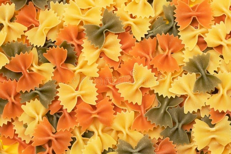 Draufsicht des rohen farfalle Teigwarenstapels lokalisiert auf gelbem Hintergrund lizenzfreie stockfotos