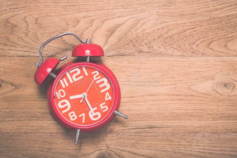 Draufsicht des roten Weckers auf altem hölzernem Plankenhintergrund lizenzfreie stockfotos