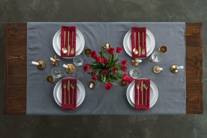 Draufsicht des rustikalen Gedecks mit rotem Tulpenblumenstrauß, getrübtem Tischbesteck, Weingläsern, Kerzen und leeren Platten au stockfoto