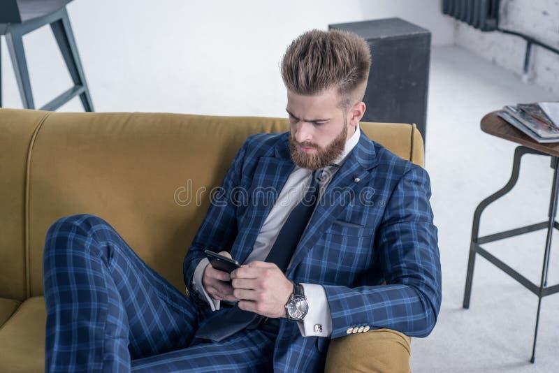 Draufsicht des schönen sexy Geschäftsmannes, der auf einem Sofa in einer Klage sitzt und sein Telefon verwendet stockfoto