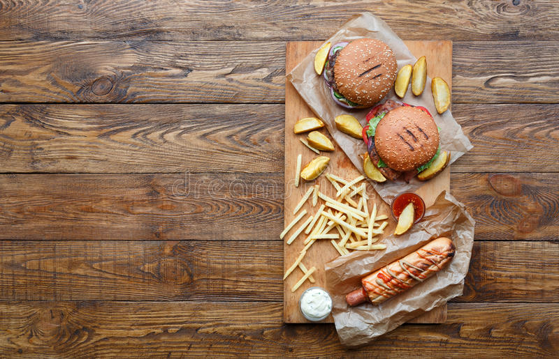 Draufsicht des Schnellimbisses über Holz Hamburger, Würstchen und Fischrogen lizenzfreie stockbilder