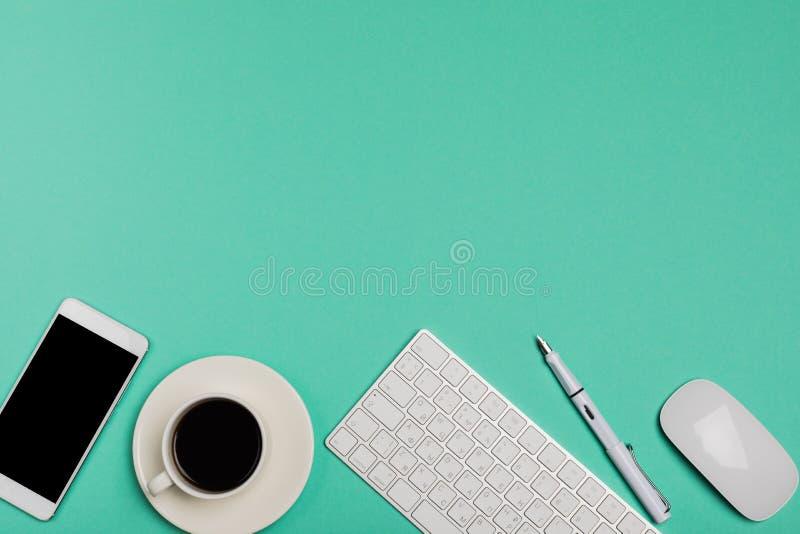 Draufsicht des Schreibtischarbeitsplatzes mit Smartphone, Tastatur, Kaffee und Maus auf blauem Hintergrund mit Kopienraum, Grafik stockfoto