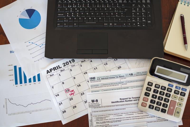 Draufsicht des Schreibtisches mit Laptop, Taschenrechner, Steuerformularen, Diagrammen und Kalender Steuer-Jahreszeit-Konzept stockfotografie