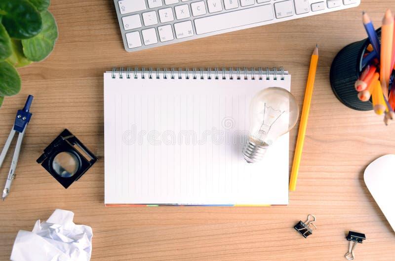 Draufsicht des Schreibtischs mit Papier, Briefpapier, Computer, Blume, leerem Notizblock und Glühlampe stockfotos