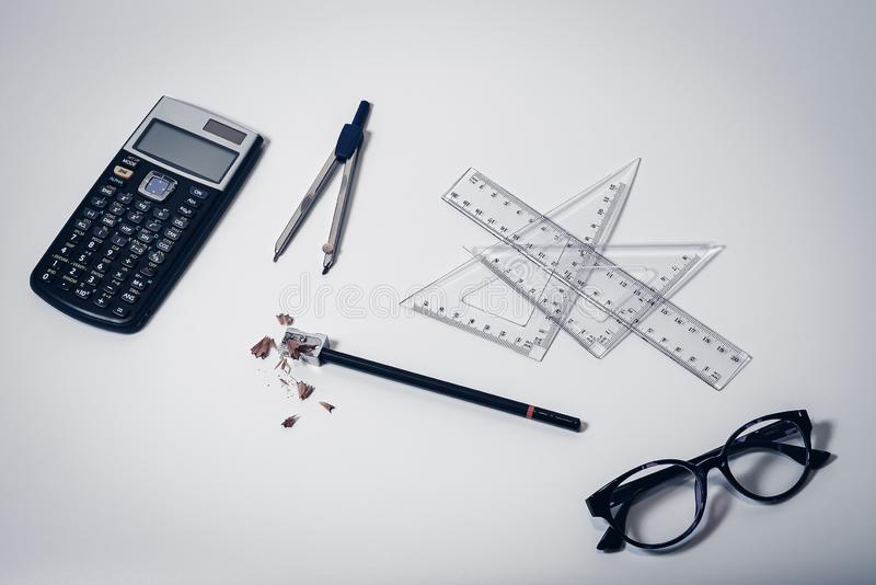 Draufsicht des Schulbedarfs auf sauberem weißem Tischplattenhintergrund mit Taschenrechner, Papierkompaß, Machthabern, Gläsern un lizenzfreie stockbilder