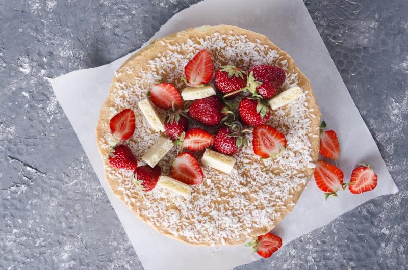 Draufsicht des Schwammkuchens, -erdbeeren und -stücke Schokolade Geschmackvoller Kuchen auf dem Backpapier lizenzfreie stockfotos