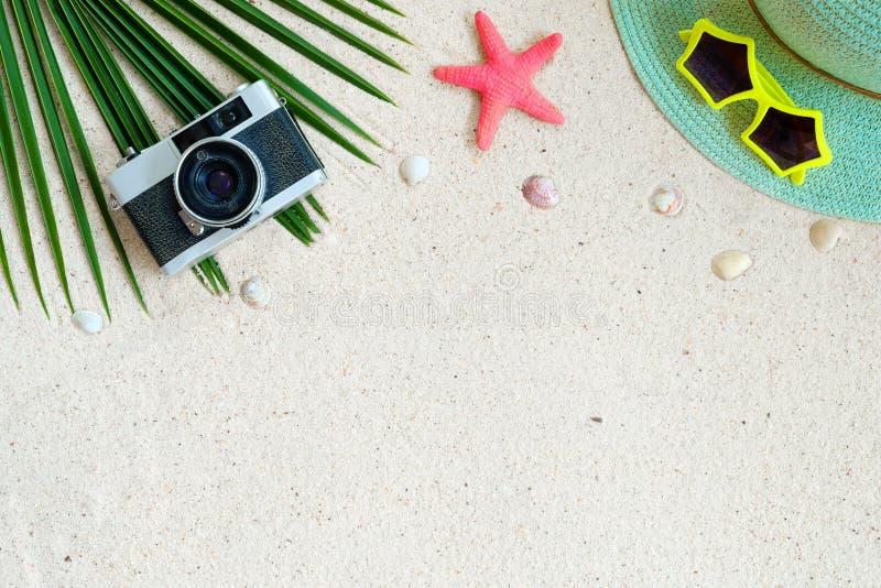 Draufsicht des Strandes versanden mit Kokosnussblättern, -kamera, -oberteilen, -Starfish, -Sonnenbrille, -oberteilen und -strohhu stockfotos