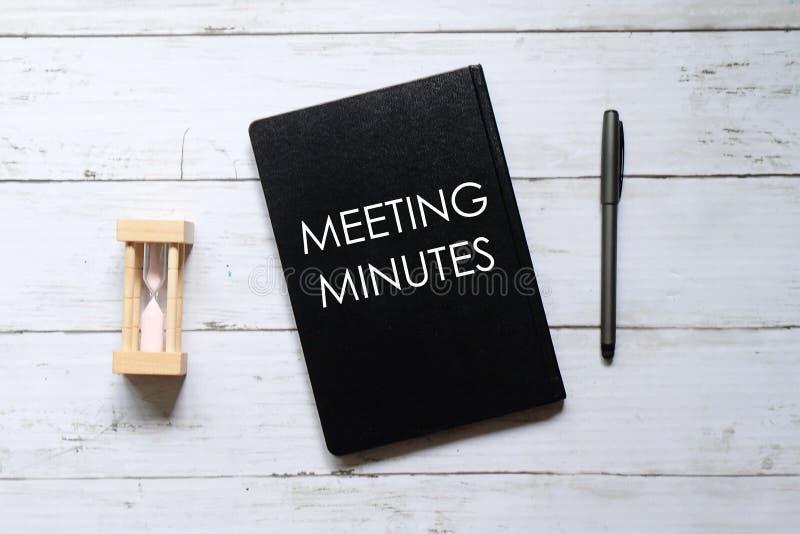 Draufsicht des Stundenglases, -stiftes und -notizbuches geschrieben mit ' SITZUNG MINUTES' auf weißem hölzernem Hinterg lizenzfreie stockfotografie